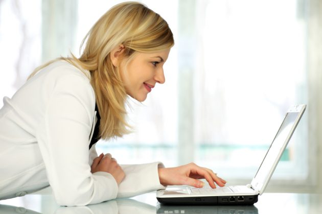 Woman typing on laptop computer.