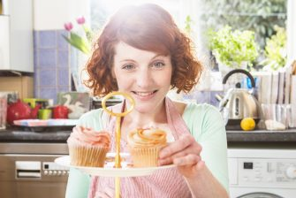Woman placing cupcake on plate in kitchen.