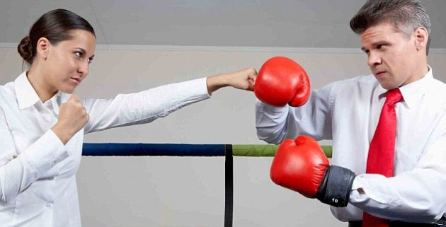 C42TMB Portrait of aggressive businessman in boxing gloves fighting with serious female