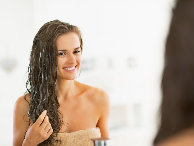 Happy young woman applying hair mask in bathroom
