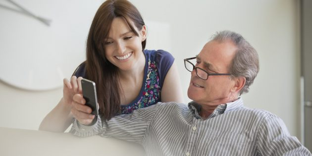 Father showing cell phone to daughter